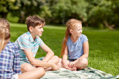 Group of happy kids or friends outdoors. Friendship, childhood, leisure and people concept - group of happy kids or friends sitting on grass in summer park Royalty Free Stock Images