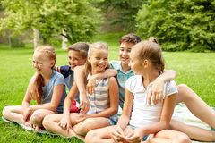 Group of happy kids or friends outdoors. Friendship, childhood, leisure and people concept - group of happy kids or friends sitting on grass in summer park Royalty Free Stock Photography