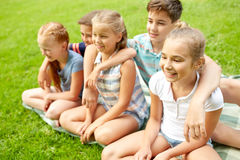Group of happy kids or friends outdoors. Friendship, childhood, leisure and people concept - group of happy kids or friends sitting on grass in summer park Royalty Free Stock Photo