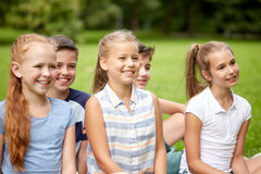 Group of happy kids or friends outdoors. Friendship, childhood, leisure and people concept - group of happy kids or friends in summer park Stock Photography