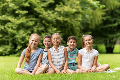 Group of happy kids or friends outdoors. Friendship, childhood, leisure and people concept - group of happy kids or friends in summer park Stock Photos
