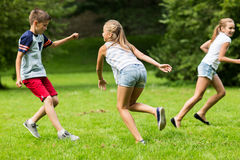 Group of happy kids or friends playing outdoors. Friendship, childhood, leisure and people concept - group of happy kids or friends playing catch-up game and Stock Images
