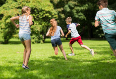 Group of happy kids or friends playing outdoors Stock Photography