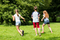 Group of happy kids or friends playing outdoors. Friendship, childhood, leisure and people concept - group of happy kids or friends playing catch-up game and Stock Photography