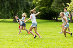 Group of happy kids or friends playing outdoors. Friendship, childhood, leisure and people concept - group of happy kids or friends playing catch-up game and Royalty Free Stock Photography