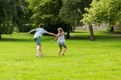 Group of happy kids or friends playing outdoors. Friendship, childhood, leisure and people concept - group of happy kids or friends playing catch-up game and Royalty Free Stock Photos