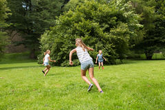 Group of happy kids or friends playing outdoors. Friendship, childhood, leisure and people concept - group of happy kids or friends playing catch-up game and Stock Photos