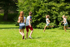Group of happy kids or friends playing outdoors Royalty Free Stock Image