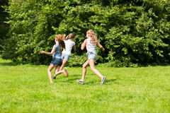 Group of happy kids or friends playing outdoors. Friendship, childhood, leisure and people concept - group of happy kids or friends playing catch-up game and Royalty Free Stock Images