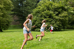 Group of happy kids or friends playing outdoors. Friendship, childhood, leisure and people concept - group of happy kids or friends playing catch-up game and Stock Image