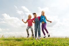Group of happy kids jumping high on green field Stock Image