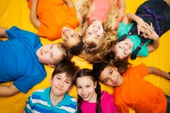 Group of happy kids laying in circle. Diversity looking Caucasian and black boys and girls smilng Royalty Free Stock Images