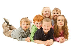 Group of happy kids laying on floor together. Group of six children laying down on other kdis on floor together. Isolated on white Stock Photo