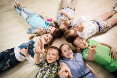 Group of happy kids. Laying in star shape on the floor with lifted hands Royalty Free Stock Image