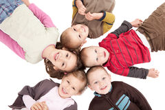 Group of happy kids lying on backs on floor. Group of happy kids lying on backs on isolated white floor Stock Images