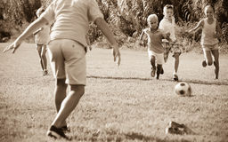 Group of happy kids playing football together on green lawn in p. Group of happy kids in school age happily playing football together on green lawn in park Royalty Free Stock Photography