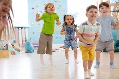 Group of happy kids playing and jumping. In daycare royalty free stock image