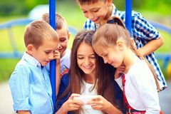 Group of happy kids playing online games together, outdoors Stock Images