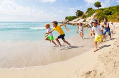 Group of happy kids racing on sandy beach. Group of happy kids racing barefoot and having fun on sandy beach in sunny weather Stock Photography