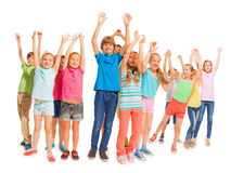 Group of happy kids with raised hands on white. Many happy kids standing in together and lift hands up in the air royalty free stock photo