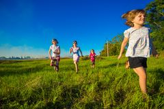 Group of happy kids running in summer field stock photo