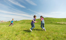Group of happy kids running outdoors Stock Images