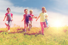 Group of happy kids running outdoors Stock Photos