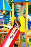 Group of happy kids sliding in colorful playground stock photography