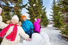 Group of happy kids throw snowballs during fight Royalty Free Stock Photography