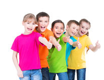 Group of happy kids with thumb up sign. Group of happy kids with thumb up sign in colorful t-shirts standing together -  isolated on white Stock Images