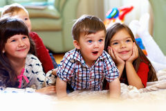 Group of happy kids watching tv at home royalty free stock images