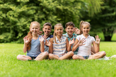 Group of happy kids waving hands outdoors Royalty Free Stock Image