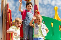 Group of happy kids waving hands on playground stock photos