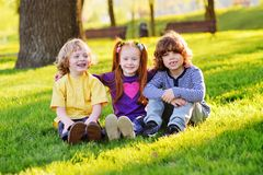 Group of happy little children smiling sitting in park on grass under a tree. royalty free stock image