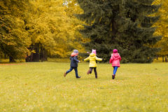 Group of happy little kids running outdoors Stock Images