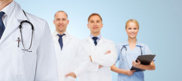 Group of happy medics in white coats. Healthcare, profession, teamwork and medicine concept - group of happy medics in white coats over blue background stock photography