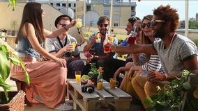 Group of happy multi-ethnic friends toasting with cocktails at rooftop party. Group of happy multi-ethnic friends looking at camera and toasting with cocktails stock video