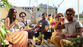 Group of happy multi-ethnic friends toasting with cocktails at rooftop party. Group of happy multi-ethnic friends looking at camera and toasting with cocktails stock video footage