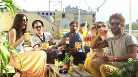 Group of happy multi-ethnic friends toasting with cocktails at rooftop party. Group of happy multi-ethnic friends looking at camera and toasting with cocktails stock footage