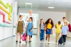 Group of happy multiethnic classmates walking. By school corridor stock photography