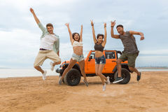Group of happy multiethnic friends jumping. In front of their car with hands raised at the beach Royalty Free Stock Photo