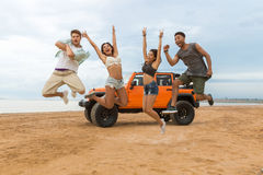 Group of happy multiethnic friends jumping. In front of their car with hands raised and having fun at the beach Royalty Free Stock Image