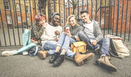 Group of happy multiracial best friends having fun using mobile phone. Group of happy multiracial best friends having fun using mobile smart phone - Young Royalty Free Stock Images