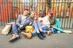 Group of happy multiracial best friends having fun using phone. Group of happy multiracial best friends having fun using mobile smart phone - Young hipster Stock Image