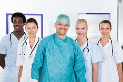Group Of Happy Multiracial Doctors. Happy Mature Doctor In Surgical Gown With His Coworkers Stock Images