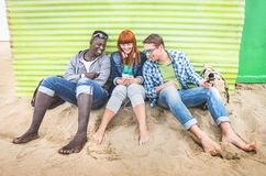 Group of happy multiracial friends having fun together using mobile phone stock photos