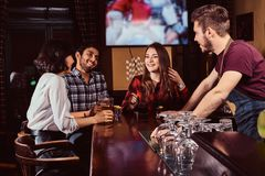Group of happy multiracial friends resting at bar and talking with the bartender. stock photography