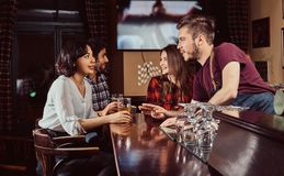 Group of happy multiracial friends resting at bar and talking with the bartender. royalty free stock photo