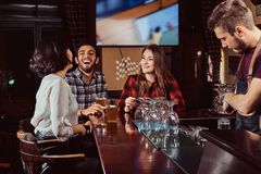 Group of happy multiracial friends resting and talking at bar or pub. stock photos