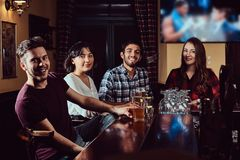 Group of happy multiracial friends resting and talking at bar or pub. stock photography